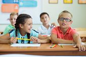Happy Elementary Students Sitting At Desk And Joyful Discussing In Classroom poster