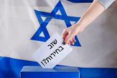 Israeli Woman Votes On Election Day. Hebrew Text Elections Again On Voting Paper Over Israel Flag Ba poster
