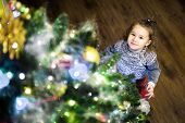 Baby Girl Stands By Christmas Tree At Home. Cute Little Child Is Eve The Christmas And New Year Holi poster