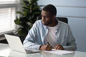 Focused African American Man Make Notes Watching Webinar On Laptop poster