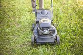 The Gardener Is Caring For The Grass. Lawn Mower Work. Green Lawn Near The House. Lawn Grass Is Cut  poster