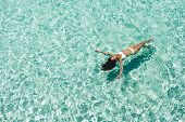 Woman In White Bikini Lying On Transparent Turquoise Water Surface On Beach. Travel And Vacations Co poster