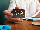 Man Holds Individual Retirement Account Ira Sign On The Black Sheet. poster