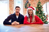 Young couple wearing santa claus hat sitting on chair and table around christmas tree at home sticki poster