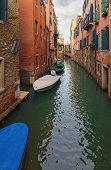 Scenic Landscape Of Typical Street Canal Between Ancient Buildings In Venice. Boats Moored Near Hous poster