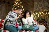 Young Couple Upset Woman And Angry Man Both Wearing Warm Sweaters Quarrelling In Room Decorated For  poster