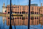 The Albert Dock In Liverpool Shot Through The Rigging Of A Boat Moored At The Side. The Liver Buildi poster