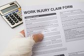 picture of hurt  - hurted hand holding a work injury claim form - JPG
