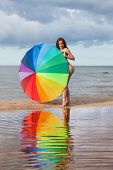 stock photo of nudism  - Young naked girl with a colorful umbrella on the beach - JPG