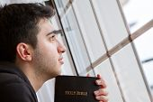 picture of salvation  - Young man looking outside with Bible in hand - JPG