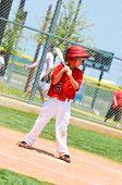 stock photo of little-league  - Little league baseball player in red jersey waiting to bat using a wood bat - JPG