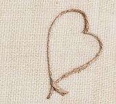 Single hemp rope heart shape on tan burlap fabric