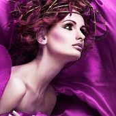 Red hairs. Portrait of beautiful girl in violet fabric in a chaplet from branches.