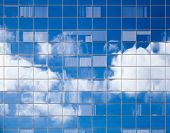 Abstract Background Texture With Bright Clouds Reflected In Windows Of Modern Office Building