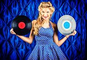 Pretty pin-up woman with retro hairstyle and make-up posing with vinyl record over vintage background.