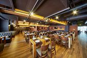 foto of public housing  - Interior of restaurant with wooden furniture and walls of red bricks - JPG