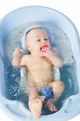 Funny baby girl bathes in a bathtube with toys