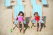 Two happy little girls lie on sun loungers and look at each other on beach at sunny day.