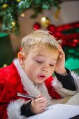 stock photo of letters to santa claus  - Adorable 5 year old boy writes to Santa Claus Christmas tree on background - JPG