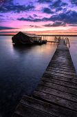 stock photo of pier a lake  - A beautiful autumn sunrise on the pebbled shores of Lake Cayuga in the Finger lakes region of New York state - JPG