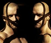 Powerful fine art portrait of two twin male models in darkness with shadows and abstract elements obscuring their faces