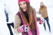 Portrait of happy girl in winterwear laughing while playing with her friends outside