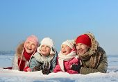 Happy parents and their kids in winterwear lying in snow