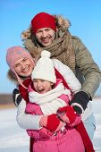 Happy parents and their daughter in winterwear outdoors