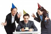 Portrait of young businessman in birthday cap looking at piece of cake with two joyful females near