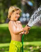 Happy young boy plays with water hose outdoors in yard during summer to cool off in hot weather