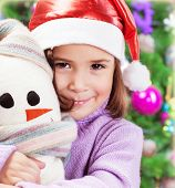 Closeup portrait of cute little girl holding snowman soft toy over Christmas tree background, wearin