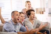 stock photo of gathering  - Cheerful group of friends watching football game on tv - JPG