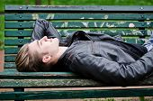 stock photo of down jacket  - Handsome blond young man lying down on green wooden park bench looking up - JPG