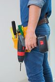 Side view mid section of a handyman with drill and toolbelt by the wall