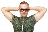 Army Soldier In Sunglasses With Hands Behind His Head