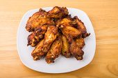 stock photo of mesquite  - Mesquite barbecued chicken wings on a square white plate and wood table - JPG
