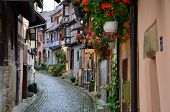 Street with half-timbered medieval houses in Eguisheim village along the famous wine route in Alsace