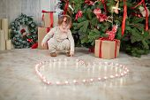 Little girl sits squatted under Christmas tree near burning tealights that stand on floor in shape o