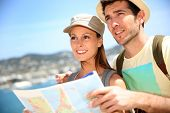 Cheerful young couple of travelers reading city map