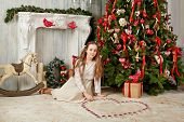 Teenage girl sits on floor under Christmas tree arranging tealights in shape of heart