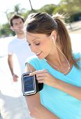 Jogger girl setting up music player