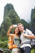 Couple taking selfie self portrait hiking on Hawaii in outdoor activity. Woman and man hiker taking