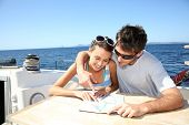 Couple on a sailboat cruise looking at map
