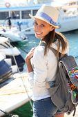 Cheerful girl getting on boat for adventure