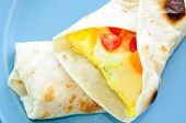 scrambled egg breakfast burrito with tomatoes and green onion an