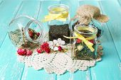 Assortment of herbs and tea in glass jars on wooden table background