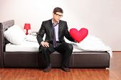 Formal man holding a red heart seated on bed indoors