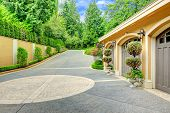 stock photo of tree trim  - Beautiful driveway with three car garage - JPG