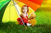 Happy smiling little girl with a rainbow umbrella in park. Child playing on green meadow. Smiling ki