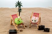 a piggy bank is located in a deck chair. symbolic photo for travel and low cost vacation